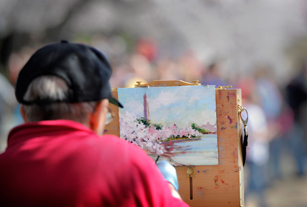Alice-Kale-of-Alexandria,-Va.,-works-on-an-oil-painting-of-cherry-blossoms-and-the-Washington-Monument