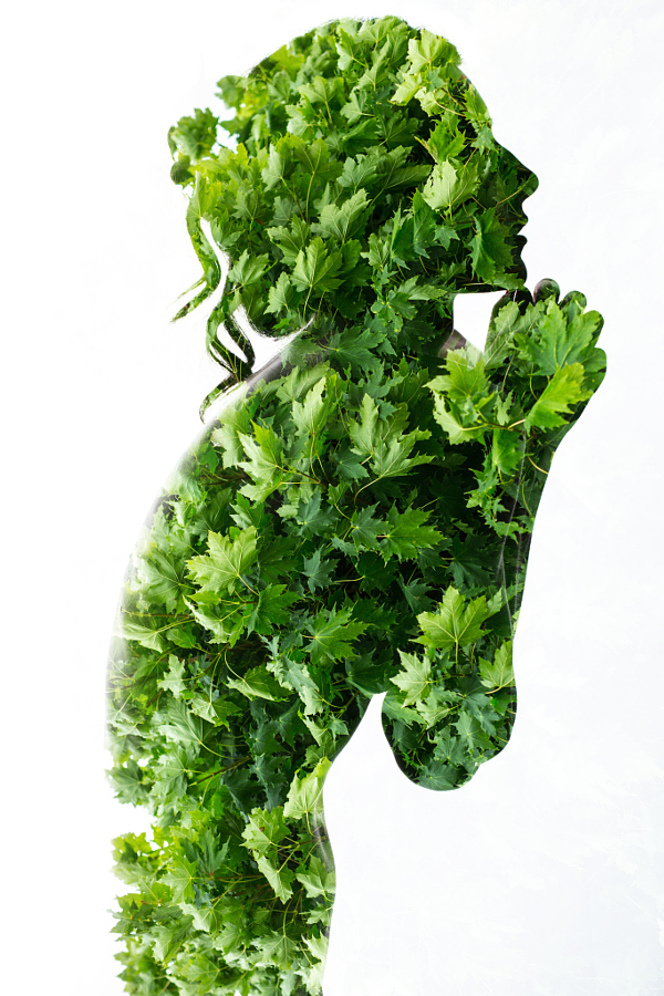 Portrait of a naked girl who tenderly clasped her hands in the face, with the effect of multiple exposure. The second frame used a picture of bright green maple leaves.