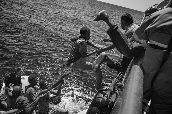 Some of the 95 migrants on board a sinking rubber dinghy frantically climb on board a rigid-hulled inflatable boat (RIB) launched to their rescue by the M.S.F. (Médecins Sans Frontières - Doctors Without Borders) Bourbon Argos search and rescue ship patrolling the Mediterranean Sea. 21 August 2015. In 2015 the ever-increasing number of migrants attempting to cross the Mediterranean Sea on unseaworthy vessels towards Europe led to an unprecedented crisis. Nearly 120 thousand people have reached Italy in the first 8 months of the year. While the European governments struggled to deal with the influx, the death toll in the Mediterranean reached record numbers. Early in May the international medical relief organization Médecins Sans Frontières (M.S.F.) joined in the search and rescue operations led in the Mediterranean Sea and launched three ships at different stages: the Phoenix (run by the Migrant Offshore Aid Station), the Bourbon Argos and Dignity.